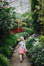 girl walking on stone path in botanical garden greenhouse with green trees, plants and colorful flowers Royalty Free Stock Photo