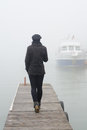 Girl walking on wooden dock on misty autumn day and boat Royalty Free Stock Photo