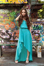 The girl at a wall young in long blue dress stands about painted graffiti Stock Photos