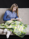 Girl in warm clothing reading a book under a blanket on the couch sitting dressed sweater and covered her Royalty Free Stock Images