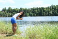 Girl washing hands in lake tropical woman smiling standing by water and her Stock Photos