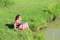 Girl washing her feet young barefoot in pink dress with black dots in a pond Royalty Free Stock Images
