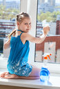 Girl washs windows on windowsill looking at camera washing Royalty Free Stock Photo
