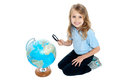 Girl watching globe through magnifying glass Stock Photography