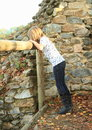 Girl watching over railings kid with long brunette hair wooden on ruins of castle Stock Photo