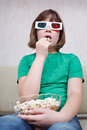 Girl watching tv movies in d stereo glasses anaglyph and eating popcorn Royalty Free Stock Image