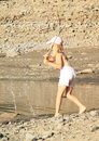 Girl with the water little barefoot in shorts and cap standing by lake and plaing wooden stick and splahsing Stock Image