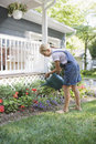 Girl watering flowers in the backyard full length side view of a house Stock Photography