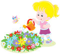 Girl watering flowers little on a flowerbed in a garden Royalty Free Stock Images