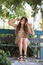 Girl wear short floral dress sitting on a bench