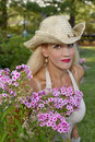 Girl wearing cowgirl hat by flowers pretty young woman outdoors flower garden Royalty Free Stock Photo
