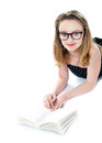 Girl wearing eyeglasses and reading book Stock Photography