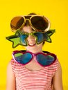Girl wearing huge glasses on yellow Stock Photos