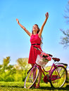 Girl wearing red dress hand up near bicycle with flowers . Royalty Free Stock Photo