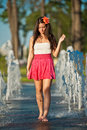 Girl wearing red skirt playing water fountain Stock Photography