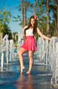 Girl wearing red skirt playing water fountain Royalty Free Stock Photo