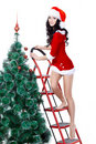 Girl wearing santa costume decorating the fur tree Stock Photography