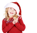 Girl wearing a santa hat holding a candy cane Royalty Free Stock Images