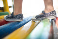 Girl wearing shoes walking on jungle gym Royalty Free Stock Photo