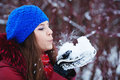 A girl wearing warm winter clothes and hat blowing snow in winte fores Royalty Free Stock Photography