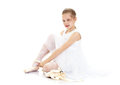 The girl wears pointe shoes beautiful blond little ballerina in white transparent dress for dancing sitting on floor and puts on Royalty Free Stock Image