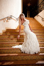 Girl in a wedding dress going down the stairs Stock Image