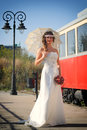 Girl in a wedding dress with umbrella standing front of the tram Royalty Free Stock Images
