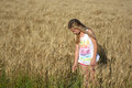 Girl in wheat field a beautiful young caucasian preteen standing a summer looking down sunshine Royalty Free Stock Images