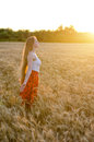 Girl in wheat field standing arms outstretched at sunset and enjoy the outdoors Royalty Free Stock Photo