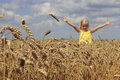 Girl in wheat field a stretching his arms to the sky Stock Photo