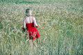 Girl in the wheat with red dress walking a golden field of Stock Photo