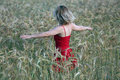 Girl in the wheat with red dress walking a golden field of Royalty Free Stock Photo