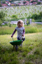 Girl with a wheelbarrow blond child in green garden Royalty Free Stock Photography