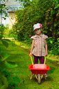 Girl with wheelbarrow little in garden Stock Photos