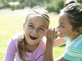 Girl whispering in friend s ear second girl gasping close up Royalty Free Stock Image