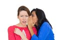 Girl whispering into her friend s ear closeup portrait of women telling something secret and disturbing shocked surprised Stock Images