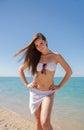 Girl in white bikini posing arms akimbo against sea Royalty Free Stock Photo
