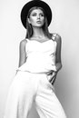 Girl in white clothes and black hat posing in studio on white background. Black and white photo Royalty Free Stock Photo