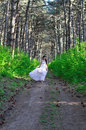Girl in a white dress goes on the wood Stock Photography