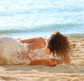 Girl in a white dress laying on beach Royalty Free Stock Photo