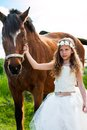 Girl in white dress leading horse cute brown on ranch Stock Photos