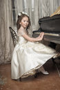 Girl in white dress at the piano a retro interior Royalty Free Stock Photography