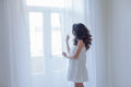 Girl in white dress stands at the window Royalty Free Stock Photo