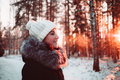 Girl in a white hat and a jacket on a background of winter forest close up photo Royalty Free Stock Photography
