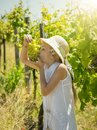 The girl in the white hat with pleasure eats green grapes on the field. Royalty Free Stock Photo