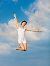 Girl in white hopping with arm raised on backgroun young woman jumping outdoors background of sky Stock Photo