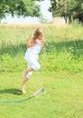Girl in white running thru sprinkler Royalty Free Stock Photo