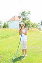 Girl in white splashing herself with garden hose barefoot little kid clothes standing and Stock Photo