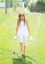 Girl in white walking thru sprinkler barefoot little with shoes hands kid clothes splashing and soaking wet Royalty Free Stock Photos