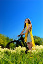 Girl among the wild flowers on a bike happy bicycle across meadow Royalty Free Stock Image